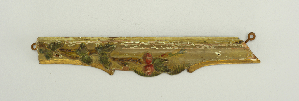 Portion of a carved Venetian moulding, painted cream, green, and red.  Flowers and fruit with running foliage.  Scrolled edge.