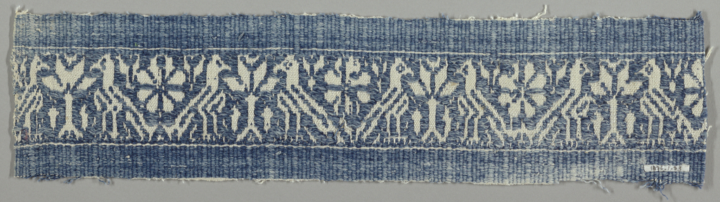 Supplementary blue weft floating alternatively face to face forming a design of affronted birds flanking a tree.