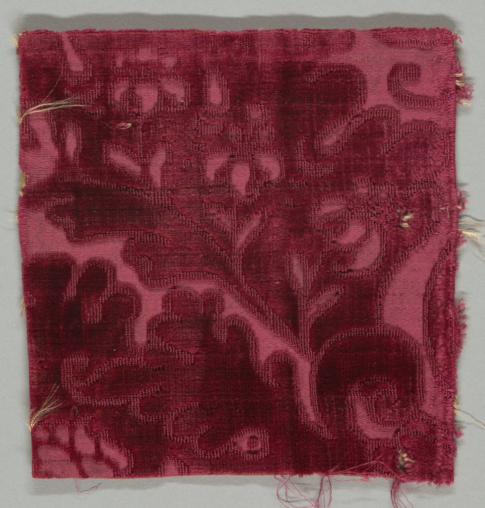 Fragment of red cut and uncut velvet on red satin ground. Portion of large-scale pomegranate motif.