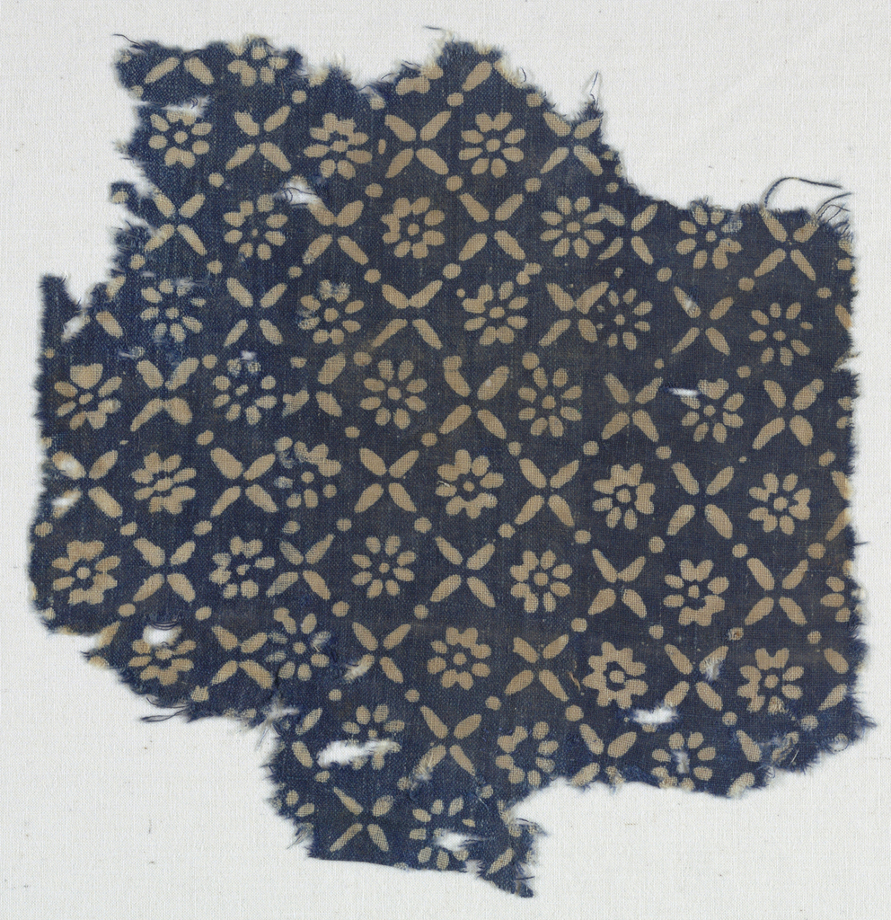Fine cotton plain weave with blue resist ground and small-scale all-over design of rosettes within squares formed by diagonally crossing lines and dots.