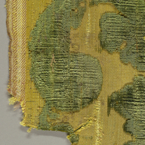 Fragment of green cut and uncut velvet on yellow silk ground. Portion of curving large-scale flower and foliage design.