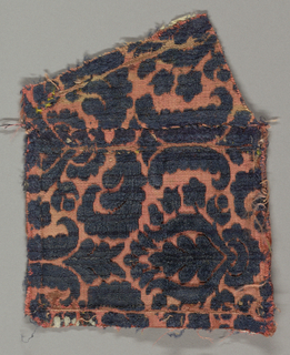 Fragment of salmon-colored twill with blue cut and uncut velvet in a symmetrical design of a highly conventionalized pomegranate. Small-scale pattern.