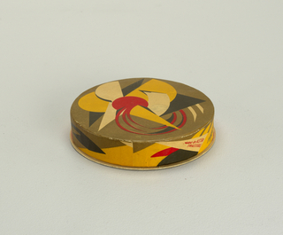 """Low, circular box and lid with printed abstract geometric decoration in olive green, yellow, red and black; the english words """"ODESSA (in red) / FOOD. TRUST (in black)"""", """"net. 4 oz."""", """"Made in U.S.S.R. (Russia)"""" printed on the side of the lid."""