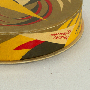Low, circular box and lid with printed abstract geometric decoration in olive green, yellow, red and black.