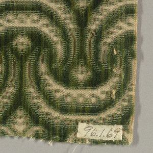 Pattern of interlocking crescents and little leaf forms reserved in tan with dark green cut and uncut pile.
