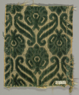 Stylized floral and leaf forms in dark green cut and uncut pile on yellow ground shot through with metal strips.