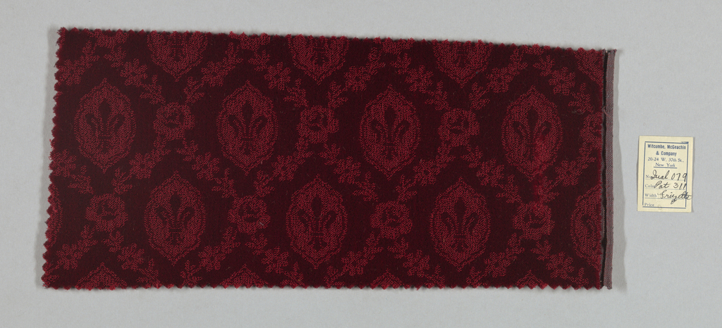 Swatch of dark red monochromatic wool velvet with a fleur-de-lis and rose garland pattern created by the juxtaposition of cut and uncut velvet.
