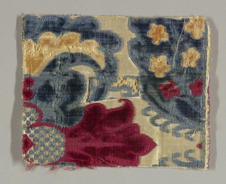 Fragment of white satin with large-scale pattern in cut and uncut blue, red and yellow velvet. Only small part of the design remains: a large-scale floral pattern.