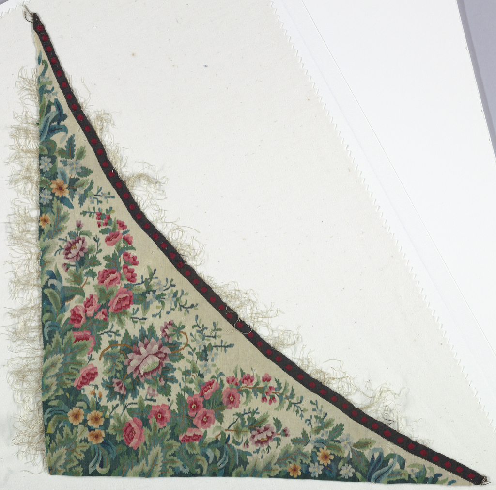 Triangular-shaped fragment with a white ground and a multi-colored design of roses and foliate. Along the upper edge is a border of dark blue with red dots. White silk threads, part of the construction, extend on two sides.