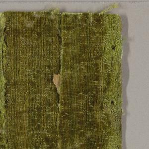 Fragment of green silk velvet. Cut pile design on uncut ground. Tiny allover pattern of highly formalized flower sprigs in outline.