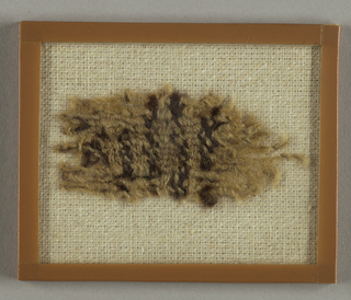 Small fragment of wool, undyed yarn and brown yarn. The undyed wool appears to be warp, but piece is too crushed to determine weave structure.