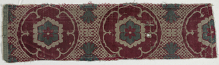 Concentric six-lobed floral medallion in red and blue-green velvet and ivory satin (voided velvet) on a speckled background of red velvet and ivory satin. The repeat is not complete, but each medallion may have had a pineapple-like appendage in blue-green velvet outlined in red velvet at top and bottom connecting it with teh staggered rows above and below.