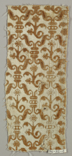 S-shapes and floral sprigs in rusty brown on white.