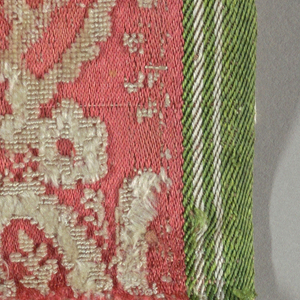 Fragment of white cut and uncut velvet on a salmon ground in a floral design.