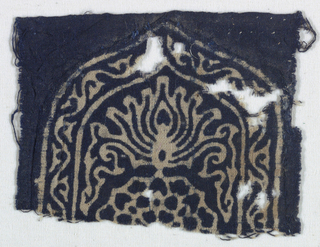 "Design is resist-printed in indigo, reserved in natural color; shows top half of a shield shape with border enclosing arabesques or vines.  A stylized lotus is inside the ""shield"" and below, half of a round petal shape is visible.  Printing on reverse is identical and equally clear."