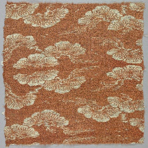 Coarsely-woven orange ground with widely spaced warp ribs has a design in reserve white of snow-covered pine branches. One narrow selvedge more tightly woven than ground.