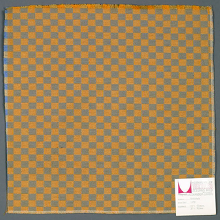 Double cloth in a light orange and gray checkerboard pattern. The warp threads are orange and ochre while the weft threads are light blue and beige. The orange warp and beige weft intersect and appear as light orange. The ochre warp and light blue weft intersect and appear as gray.
