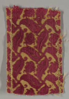 Fragment of magenta-colored velvet, cut and uncut, against a gold-colored ground in a small serpentine leaf pattern.