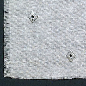 Plain weave in white with grey embroidered diamonds. Diamonds have a small hole in the center.