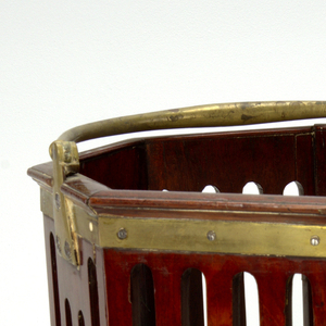 Octagonal mahogany pail with straight sides. Four vertical openings cut in each side. Gilt brass band below molding at top. Semi-circular hinged bronze carrying handle, tapering towards ends.