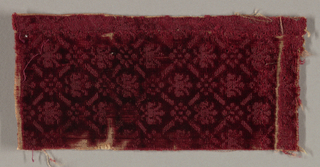 Fragment of dark magenta silk velvet, cut and uncut, in a small floral pattern set within a repeating diamond shape.