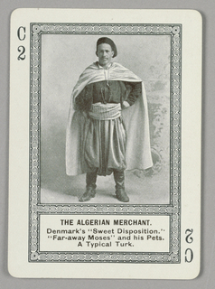"Rectangular format playing card with rounded edges, printed in black and white only. Part of a series of cards from an educational game featuring half-tone reproductions of people in national costumes from different countries around the world. Within rectangular swirling border, a photoillustration of a male figure in exotic non-Western costume, wearing boots, a hat, and a long cape. Below the image, printed in black ink: THE ALGERIAN MERCHANT. / Denmark's ""Sweet Disposition."" / ""Far-away Moses"" and his Pets. / A Typical Turk.; at upper left and lower right: C / 2"
