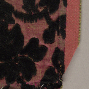 Rectangular table-mat formed by 32 small rectangular patches joined by hand in regular rows.  Various striped of floral silk and/or cotton voided cut velvets on variously patterned cloth grounds of contrasting color.  Variety of colors, with black dominating.