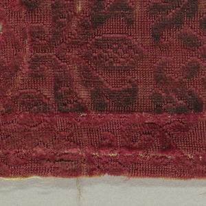 Fragment of dark red velvet with an uncut ground and design in cut pile. Small pattern of swinging branches and leaves forming ogive-shaped areas, in each a highly formalized floral motif.
