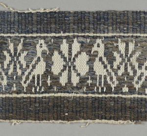 Supplementary blue weft floating alternatively face to face creating a design of birds flanking a rosette.