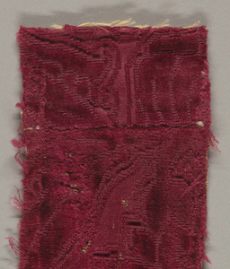 Fragment of dark red cut and uncut velvet on red satin ground. Very little pattern shows; only a portion of a floral design.
