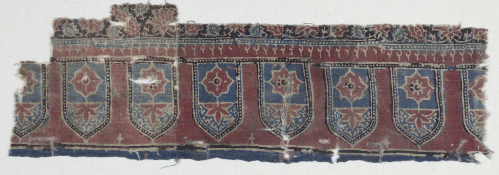 Horizonal band of Mihrabs each enclosing a simple floral motif with narrow pearled borders and a continuous pearled baseline.  Below is another pearl band off-setting the scrolling floral pattern.  Red, blue and aubergine (blue over red) and reserved areas of white.