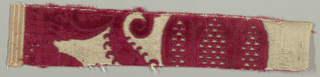 Narrow fragment of red cut and uncut velvet on white ground with extra weft of metallic thread. Fragment shows part of a large-scale floral motif.