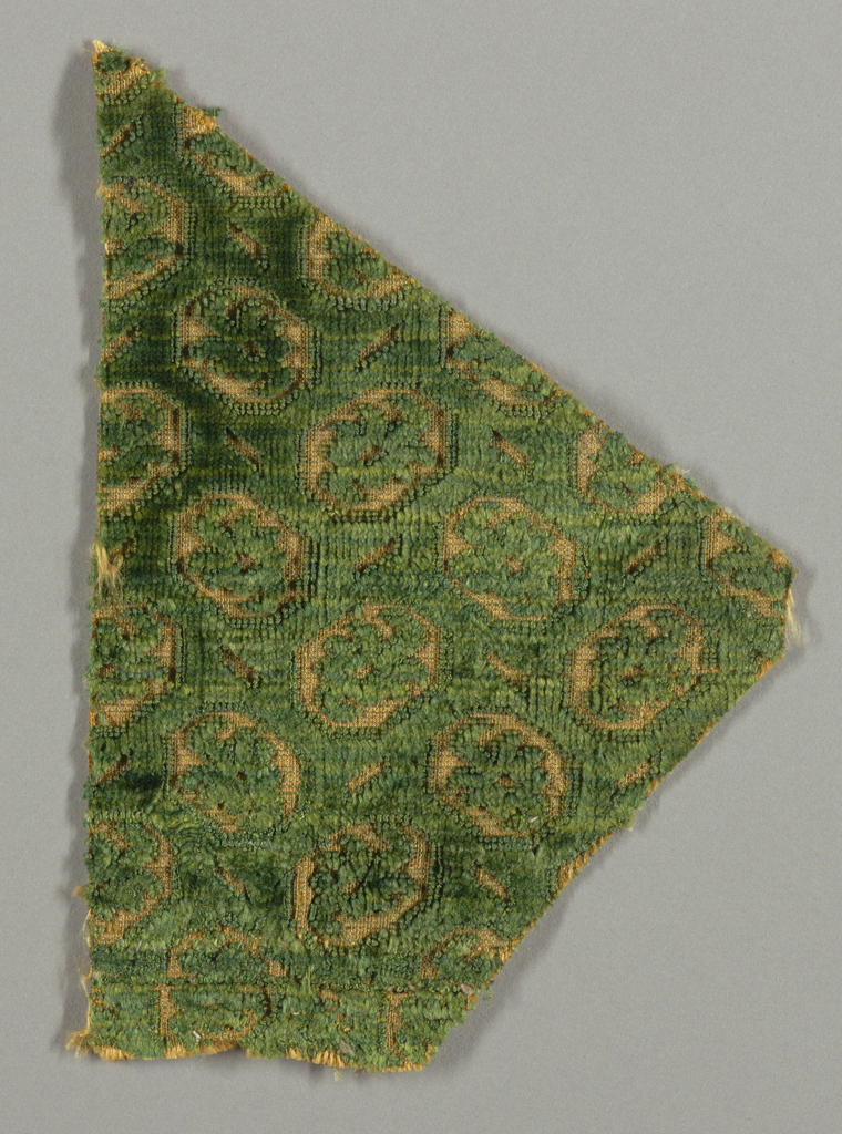 Fragment of green cut and uncut velvet on an orange-tan ground. Surface broken up into eight-sided spaces, each enclosing a tiny flowering branch.