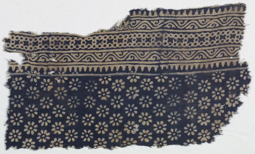 Fragment of panel with rosette-patterned field and three-part curving vine and floral borders. White design on blue ground.