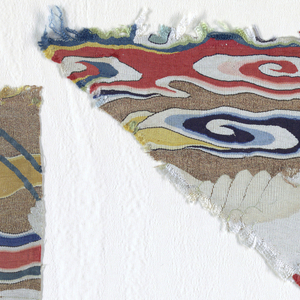 Fragments of a rank badge showing white birds in front of polychrome clouds.