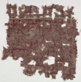 Unbleached plain weave cotton.  Design in red and dull brown (possibly faded purple), stylized branch with pointed leaves; curved stem alternates with two types of fleuron formed of flower heads in profile.  Remains of border in simple block pattern.