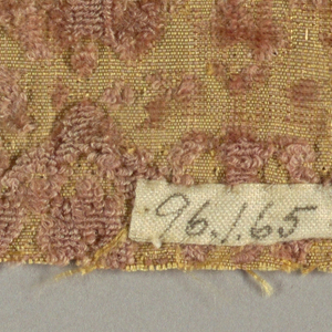 Pattern of small stylized leaf froms within horizontal zigzag rows. Pattern in pinkish tan on dull yellow ground.