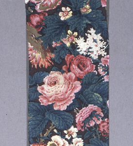 Long, narrow fragment with an allover design of large scale naturalistically drawn flowers: roses, poppies, etc. Block printed in reds, blues, drab green and faded yellow against against a plum-colored background. Considerable over-printing with yellow and blue producing green, but yellow is much faded. Repeat incomplete.