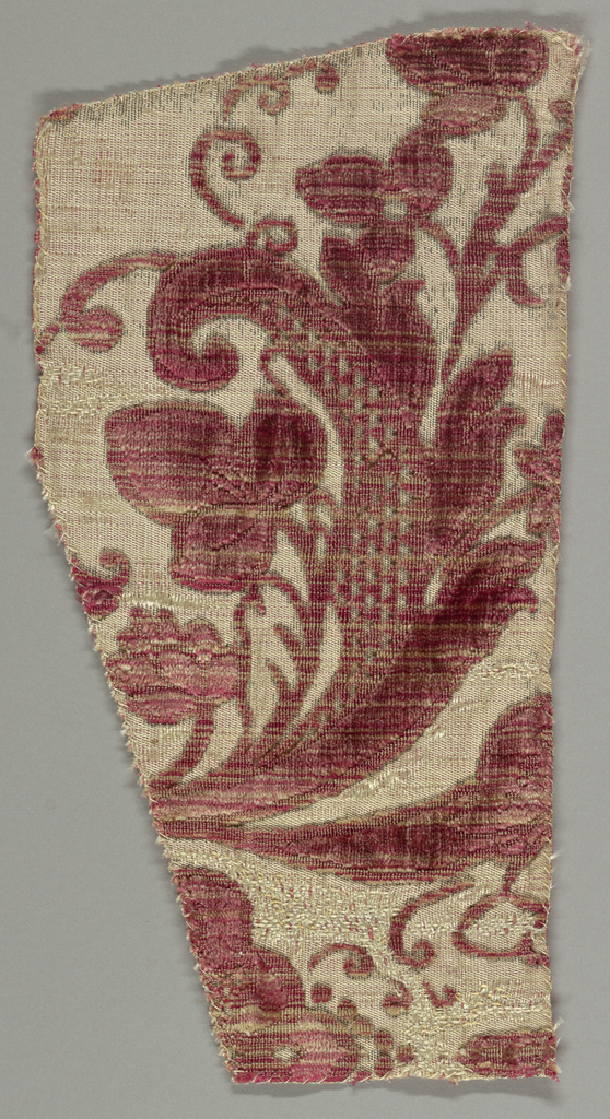 Fragment of a larger pattern showing a floral spray with infilling of triangles in rose. Traces of silver metallic.