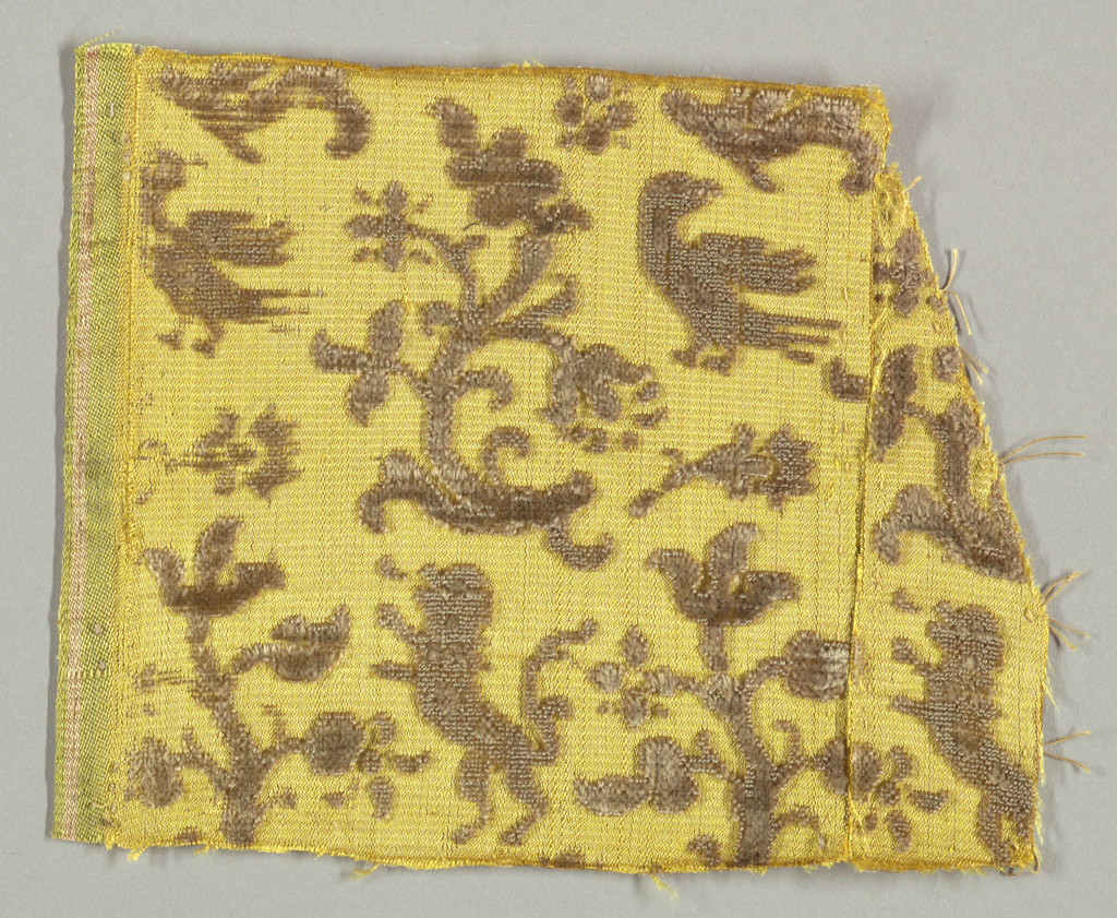 Animals, birds and plant forms in brown/purple on yellow. Selvage with green and white edge at left.