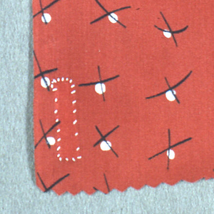 Sample of silk with a red ground printed in a design of a small white circles crossed with uneven X-marks.