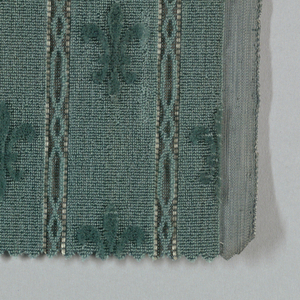 Swatch of teal blue monochromatic wool velvet with a fleur-de-lis pattern and stripe effects that are created by the juxtaposition of cut, uncut and voided velvet.