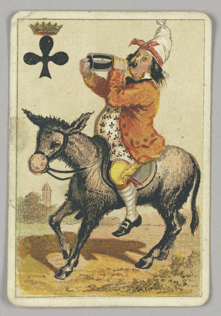 King of Clubs court playing card from a pack of transformation playing cards. A male figure riding a donkey wearing a shirt patterned with clubs and a tall white hat decorated with a red ribbon. He drinks from a bottle of alcohol. Some indications of town and landscape in the background. At upper left corner, a black club topped by a crown.