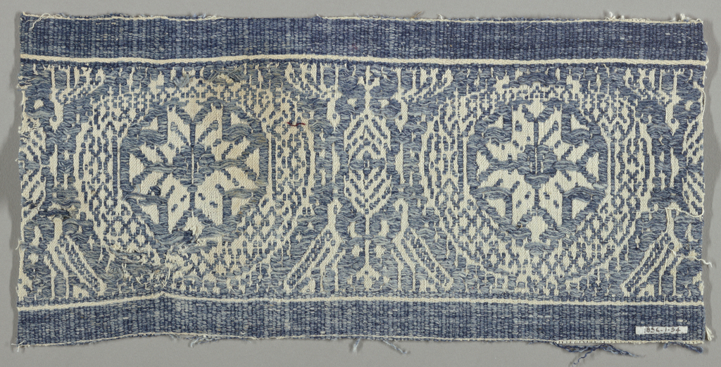 Supplementary blue weft floating alternatively face to face creating a pattern of quatrefoil rosettes.