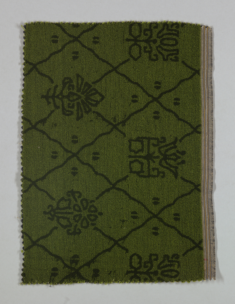 Swatch of green wool velvet with a darker green stylized floral design that created by the juxtaposition of cut and uncut and velvet .