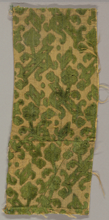 Fragment of green cut and uncut velvet on a tan ground originally heavily shot through with fine strips of flat metal. Design of small flowering branches in horizontal rows turning alternately left and right.