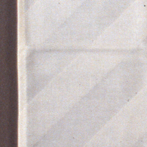 Hemmed napkin with machine-made buttonhole in one corner and Lufthansa woven into opposite corner. Damask pattern makes diagonal lines.