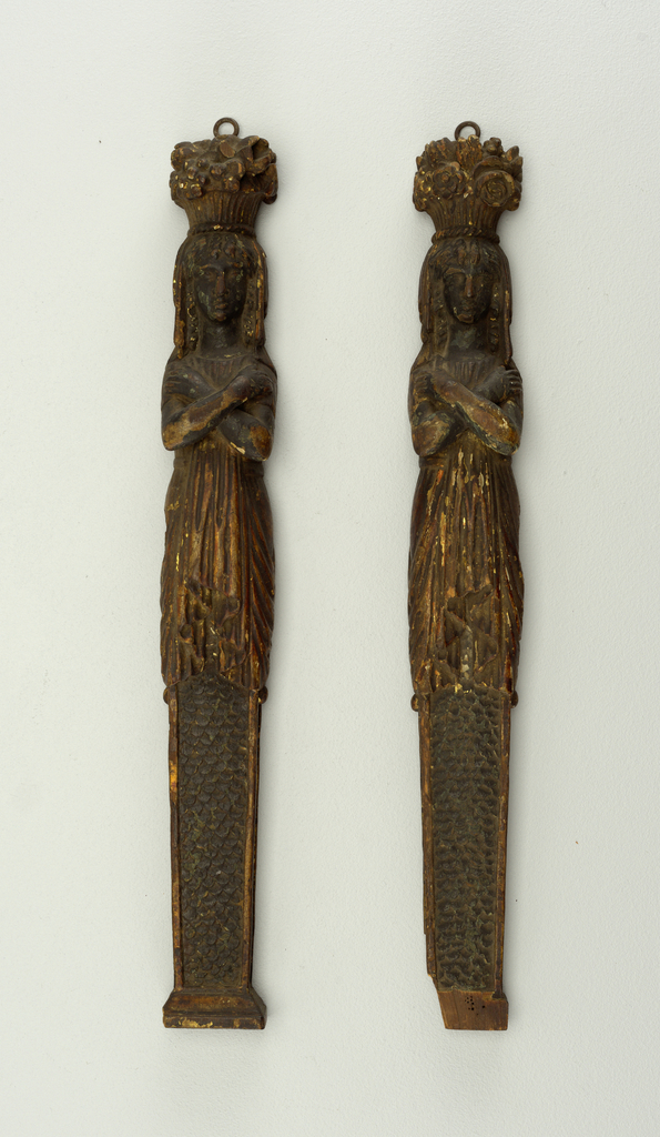Two mounts from a piece of furniture, in the form of female Gaines with imbricated sheaths, each with a flower basket upon the head. Finished on only three sides.