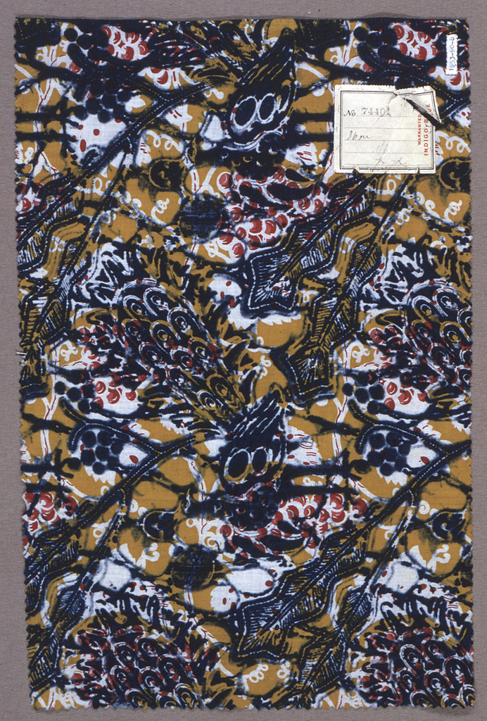 Length of printed cotton with a pattern of clusters of grapes and vines in two shades of red on a golden yellow ground. Coarsely overprinted in blue with peacocks and fantastic large leaves.