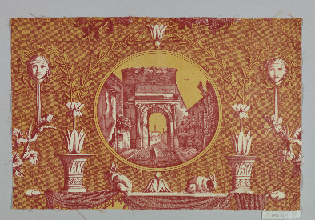 Fragment shows round medallion containing a street scene with a figure walking toward a Classical-style archway.  Surrounding the medallion are urns, masks, rabbits, acanthus leaves and drapery. In red and yellow on white ground.